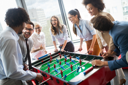 Colleagues playing table football in the break. Stock Photo