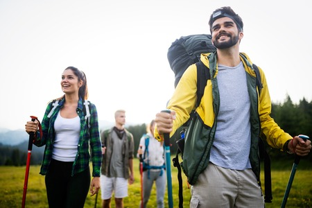 Adventure, travel, tourism, hike and people concept - group of smiling friends with backpacks and map outdoors Imagens