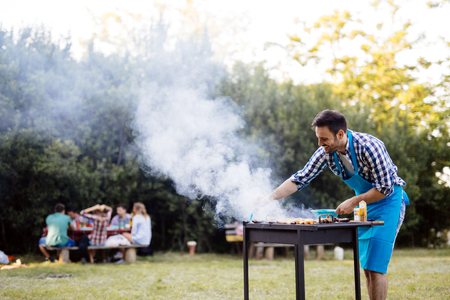 Handsome young male preparing barbecue in nature Фото со стока