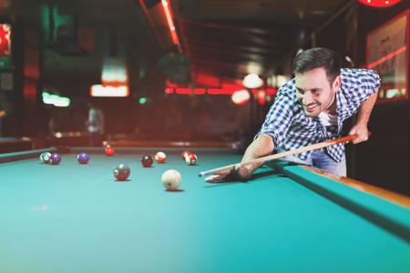 Hansome man playing pool in bar alone Фото со стока