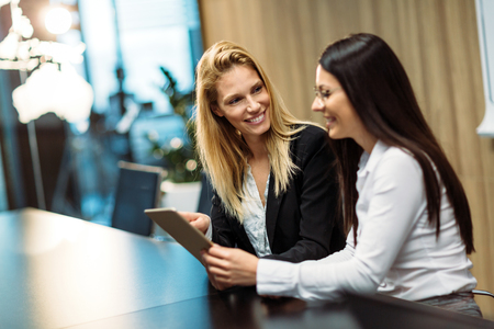 Portrait of two attractive businesswomen using tablet in office Stock Photo