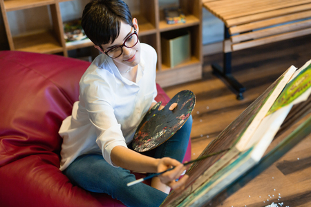 Female artist painting with palette and paintbrush Фото со стока - 119682398