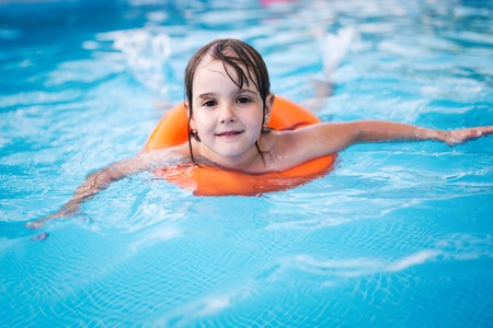 Little girl in swimming pool with float ring