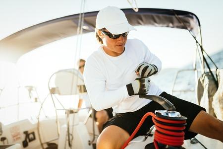 Donna forte attraente che naviga con la sua barca