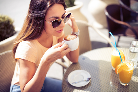 Young pretty woman drinking cappuccino, coffee in cafe outdoors 版權商用圖片