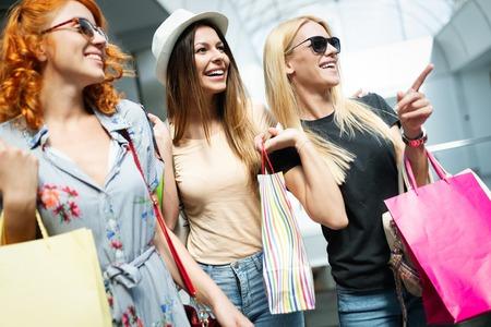 Gruppo di amici sorridenti felici che fanno shopping in città Archivio Fotografico