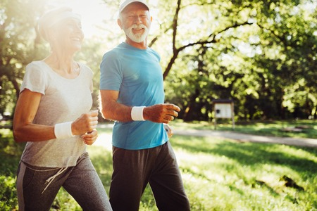 Happy senior people jogging to stay helathy and lose weight Stock Photo
