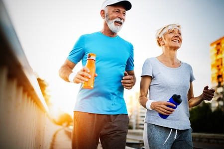 Happy senior couple staying fit by sport running Imagens