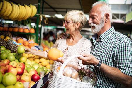 Hoger familiepaar dat biovoedselfruit en groente op de markt kiest tijdens wekelijks winkelen Stockfoto