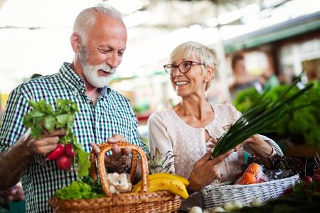 Concepto de compras, comida, venta, consumismo y personas - feliz pareja senior comprando alimentos frescos