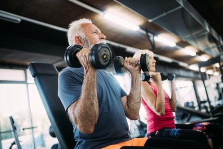 Colocar pareja madura haciendo ejercicio en el gimnasio para mantenerse saludable