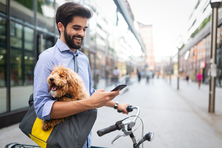 Hombre guapo feliz con bicicleta con móvil al aire libre