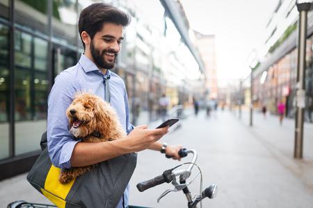 Uomo bello felice con la bicicletta che utilizza il cellulare all'aperto
