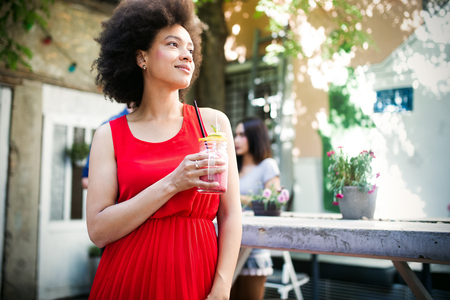 Summer lifestyle fashion portrait of stylish black woman with drink