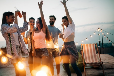 Grupo despreocupado de amigos felices disfrutando de la fiesta en la terraza de la azotea