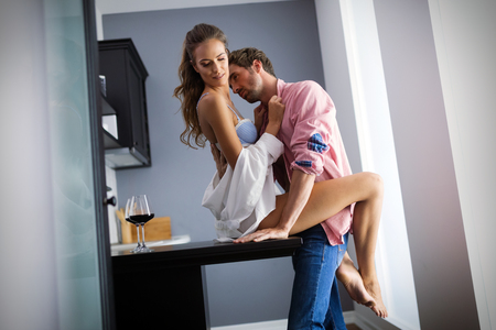 Attractive passionate couple is having on kitchen.