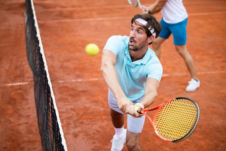 Adatta la gente felice che gioca a tennis insieme. Concetto di sport Archivio Fotografico