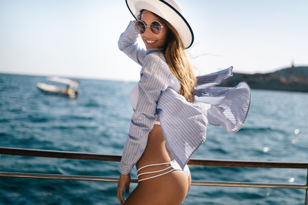 Beach vacation. Beautiful woman in sunhat and bikini enjoying summer trip Foto de archivo - 121687398