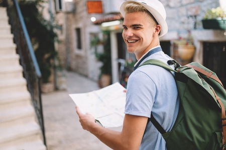 Young happy tourist with map traveling on summer vacation