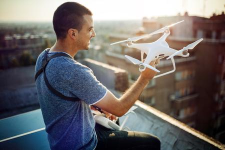 Joven técnico volando drone UAV con control remoto en la azotea