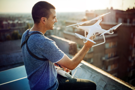 Young technician flying UAV drone with remote control on rooftop Stockfoto - 122451401