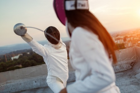 Two fencing athletes people fight on rooftop outdoors 写真素材