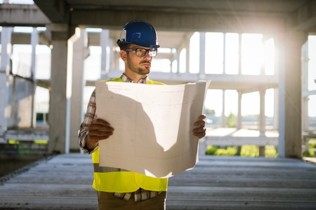 Portrait of male site contractor engineer with hard hat holding blue print paper 版權商用圖片