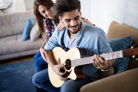 Young handsome man playing guitar for his girlfriend Zdjęcie Seryjne