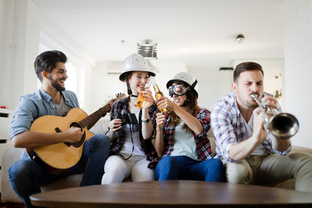 Friends having fun and partying in house and playing music