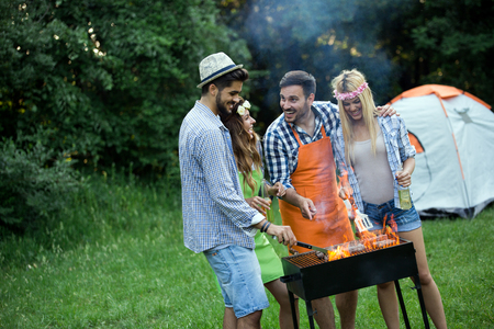 Group of friends having fun in nature doing bbq