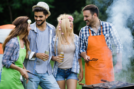 Group of happy friends having outdoor barbecue laughing together