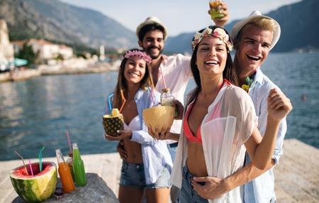Grupa przyjaciół bawi się na letniej imprezie i pije koktajl