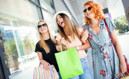 Gruppo di amici sorridenti felici che fanno shopping in città