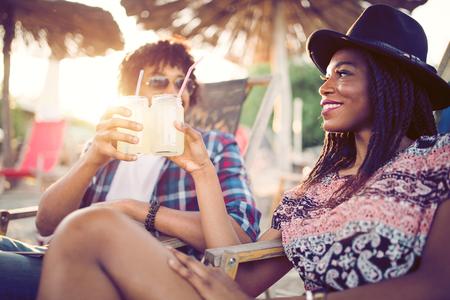 Heureux couple noir sur la plage tout en se relaxant sur leurs transats