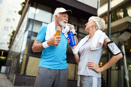 Mature couple drinks water to replenish energy and to hydrate Imagens