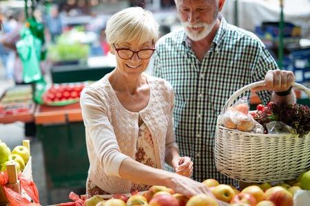 Portrait of beautiful elderly couple in market buing food