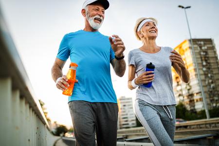 Concepto de fitness, deporte, personas, ejercicio y estilo de vida - pareja senior corriendo