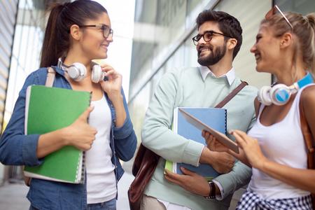 Estudiantes universitarios jovenes felices que estudian juntos. Grupo de amigos multirraciales en la universidad