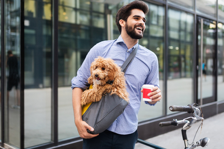 Handsome business man on street drinking coffee with dog