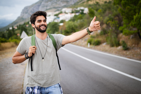 Travel man backpacking hitchhiking on road trip hitching a ride from car