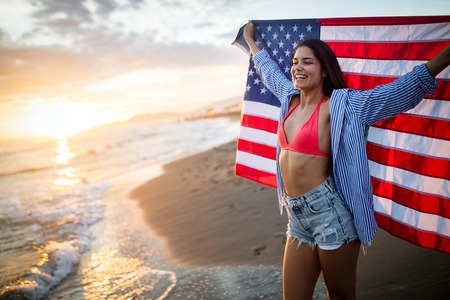 Happy woman running on beach while celebrateing independence day and enjoying freedom in USA Standard-Bild