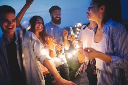 Amis heureux avec des boissons grillant à la fête sur le toit la nuit