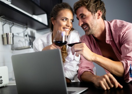 Young couple relaxing in kitchen with wine and laptop. Love, technology, people concept. Stock Photo