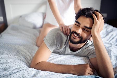 Mujer joven está haciendo su masaje novio guapo y sonriendo mientras descansan en casa