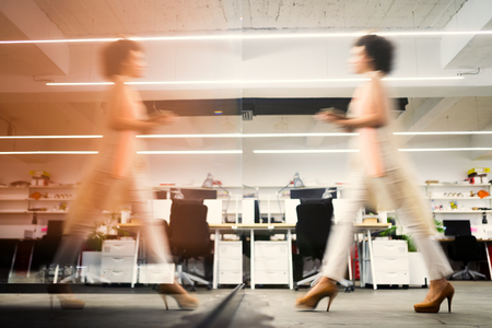 Professional business woman in motion with blur in business office Imagens