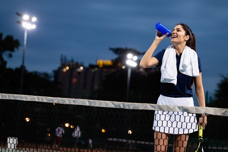 Sporty woman drinking water after tennis training Stock Photo