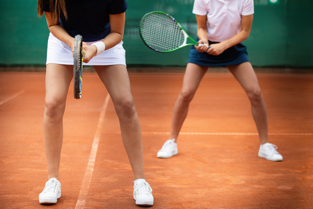 Young happy fit women playing tennis on tennis court Фото со стока