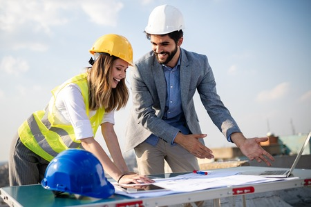 Team of architects and engineer in group on construciton site check documents and business workflow Imagens