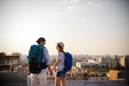 Couple de voyageurs multiethniques utilisant la carte ensemble par beau temps
