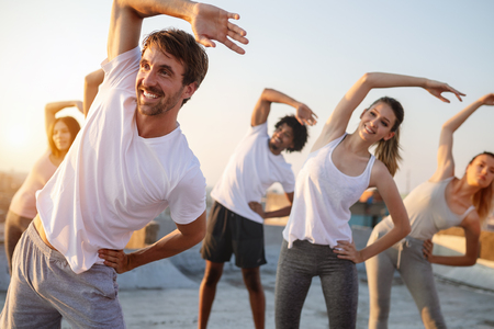 Group of athletic young people, friends in sportswear doing exercises. Sport outdoors